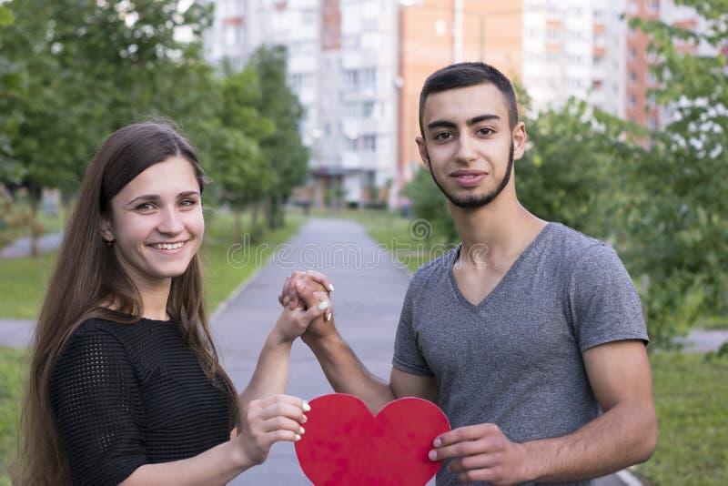 Deux jolies personnes de sourire dans l'amour avec le coeur forment images libres de droits
