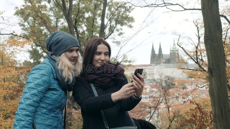 Deux jolis et jeune femme heureuse faisant Selife avec le téléphone portable en Autumn Park Les meilleurs amis font le selfie photographie stock libre de droits