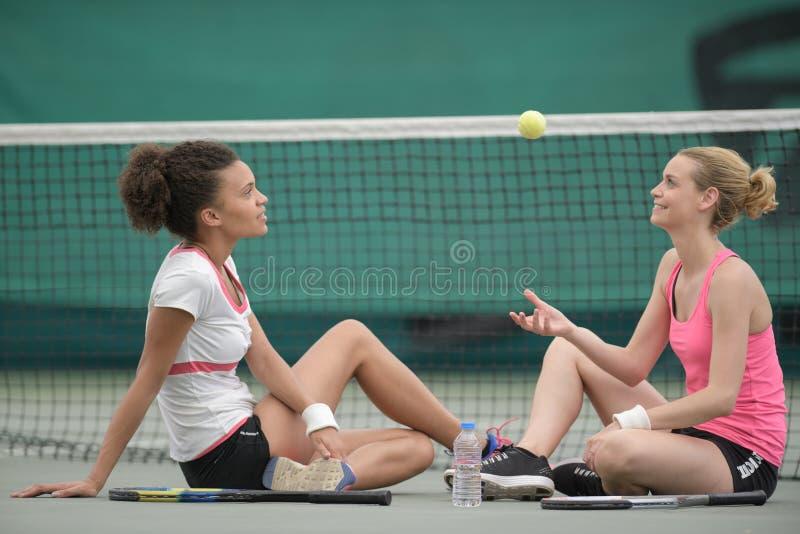 Deux jolis joueurs de tennis s'asseyant sur la cour après match images libres de droits