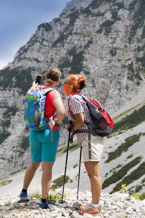 Deux jolis randonneurs de femmes photographiant un selfie sur la crête de montagne image stock