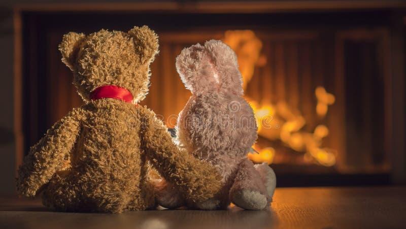 Deux jouets de peluche sont chauffés près de la cheminée photo stock