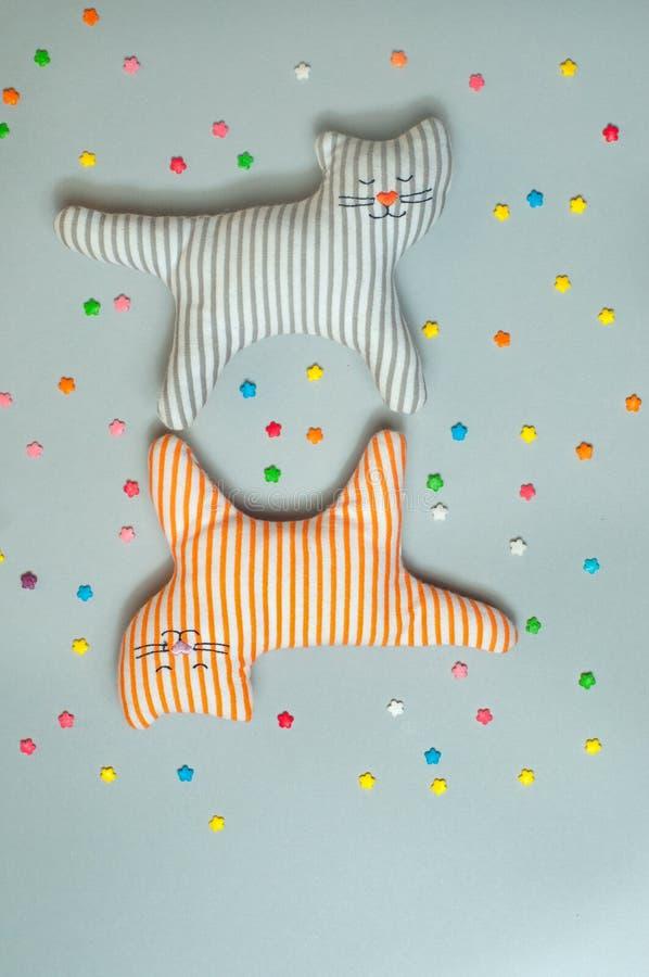 Deux jouets drôles de chat de textile au-dessus de fond gris image libre de droits