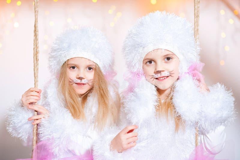 Deux jumelles de soeurs dans les costumes des caniches de chien pendant la nouvelle année Le maquillage est comme un chien Portra photos stock