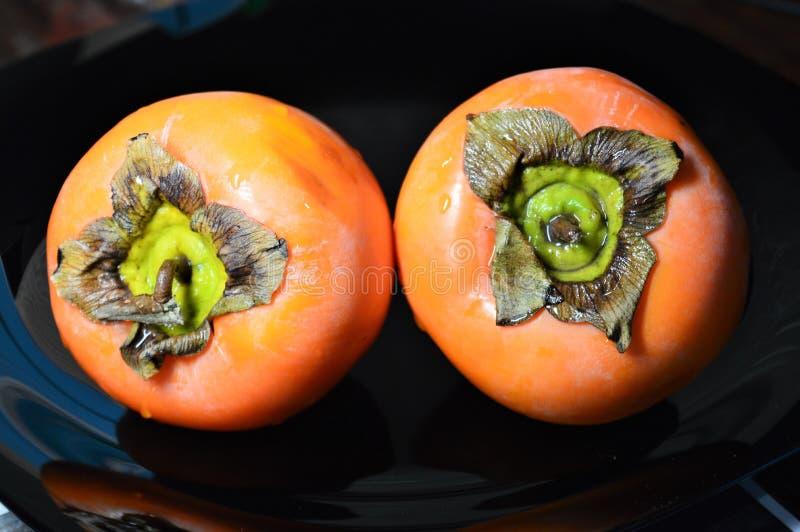 Deux kakis oranges d'un plat noir de lustre image stock