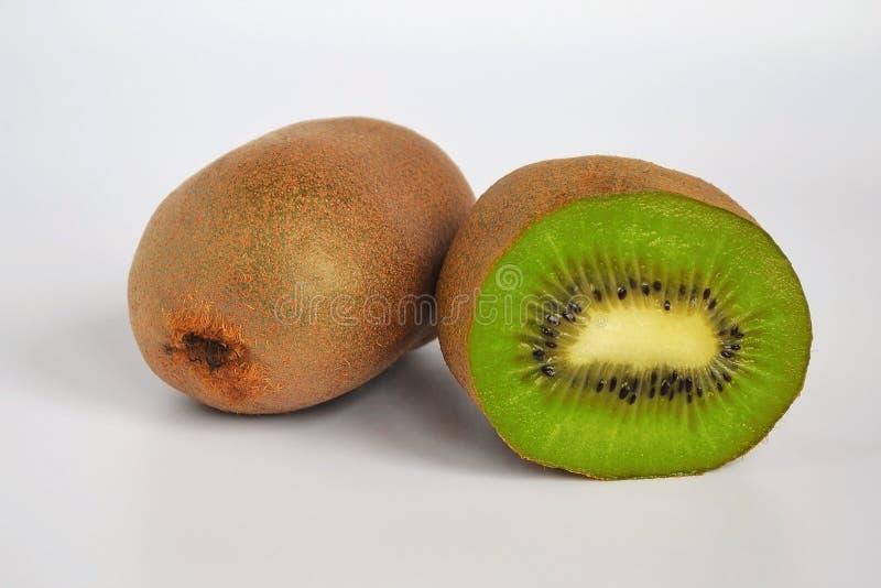 Deux kiwis : on est non épluché avec la peau brune et est en second lieu demi, sain concept de consommation sur le fond blanc images stock