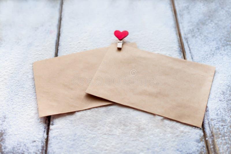 Deux l'enveloppe de l'agrafe de papier d'emballage sous forme de coeur dans la neige le jour du ` s de Valentine, attitudes du `  photos stock