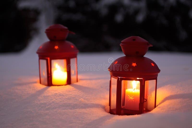 Deux lanternes brûlantes dans la neige image stock