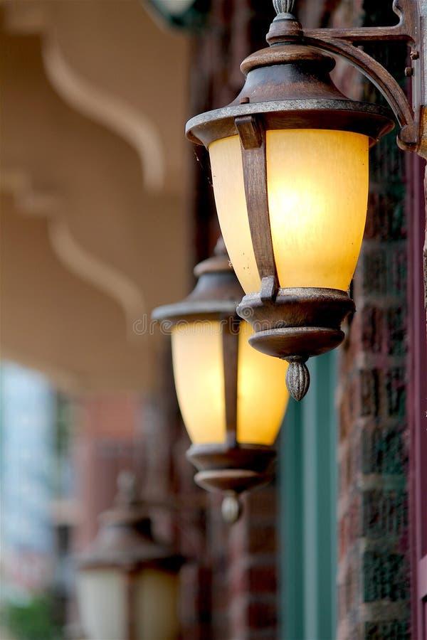 Deux lanternes de cuivre en dehors de devanture de magasin de brique dans la ville historique photographie stock libre de droits