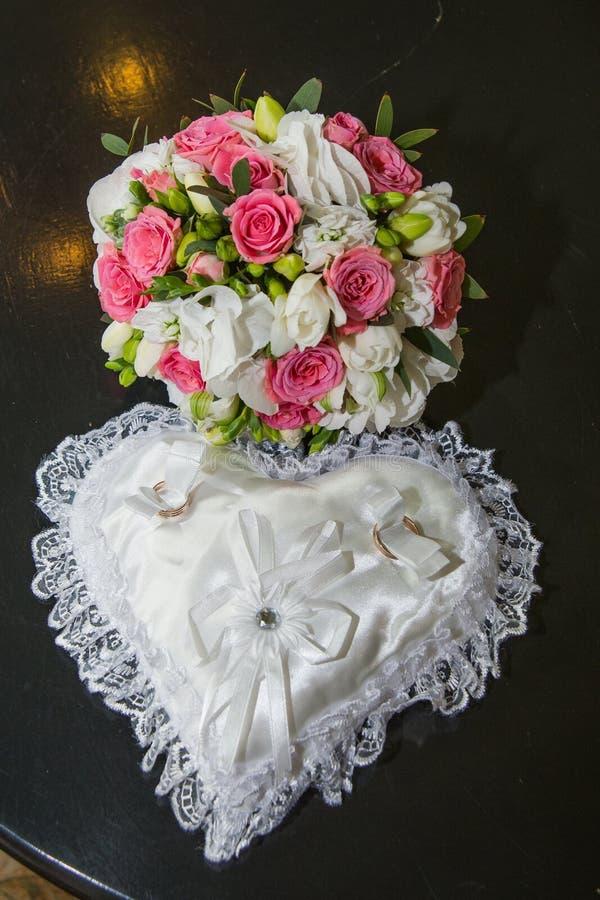 Deux les épouser d'anneaux, oreiller sous forme de coeur, un bouquet des roses rouges et blanches photographie stock libre de droits