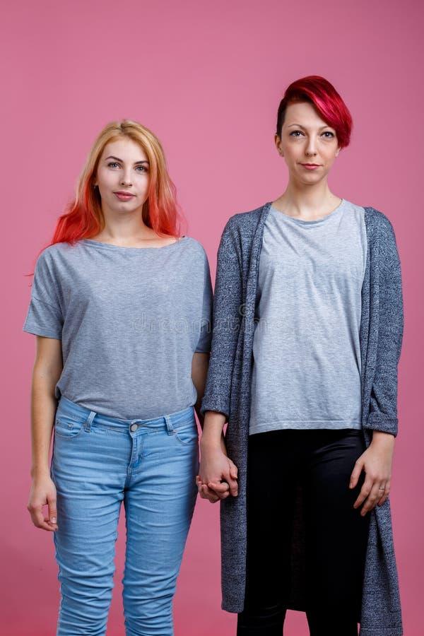 Deux lesbiennes tiennent des mains et regardent directement un fond rose photos libres de droits