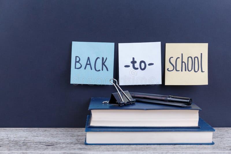 Deux livres, sur lesquels est un marqueur et une bride et les morceaux de papier avec l'inscription de nouveau à l'école image stock
