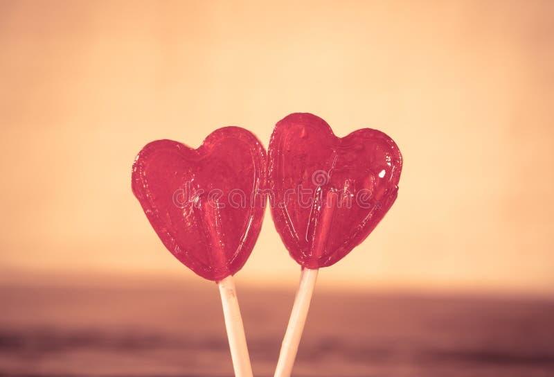 Deux lucettes en forme de coeur rouges comme métaphore concept de l'amour, de l'unité et de valentines de jour images stock