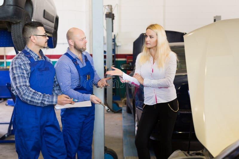 Deux mécaniques essayant de tricher le client à l'atelier image stock