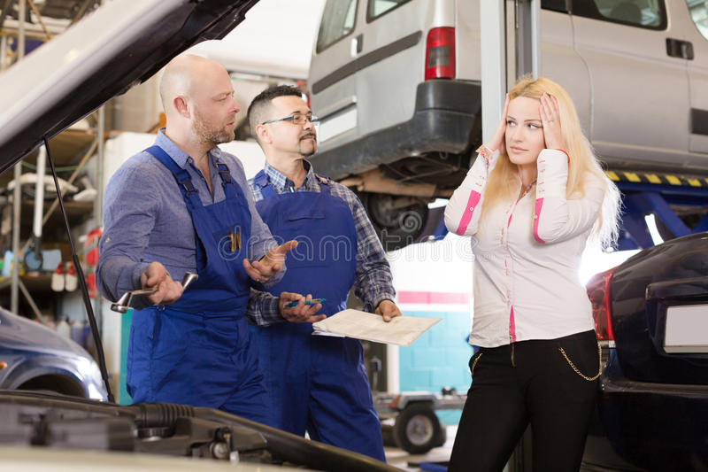 Deux mécaniques essayant de tricher le client à l'atelier images stock