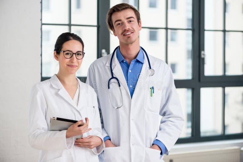 Deux médecins consacrés souriant à l'appareil-photo images stock