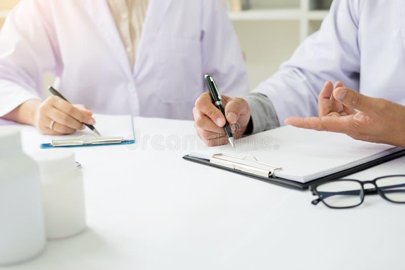 Deux médecins discutant les notes patientes dans un bureau indiquant a image stock