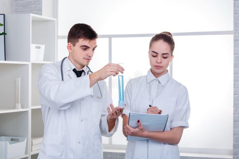 Deux médecins, la fille écrit quelque chose dans un carnet, et le type regarde le flacon liquide bleu photos stock