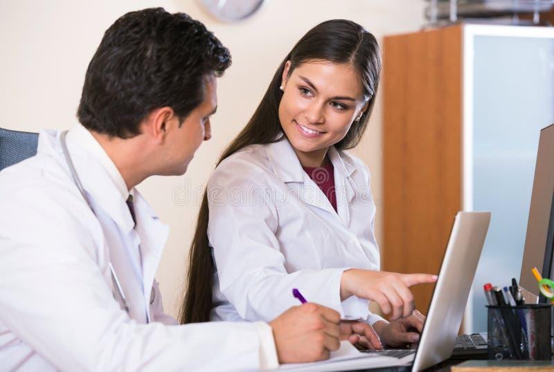 Deux médecins professionnels faisant un brainstorm et partageant l'information photos stock