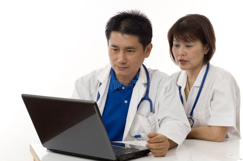 Deux médecins regardant l'ordinateur sur leur bureau images stock