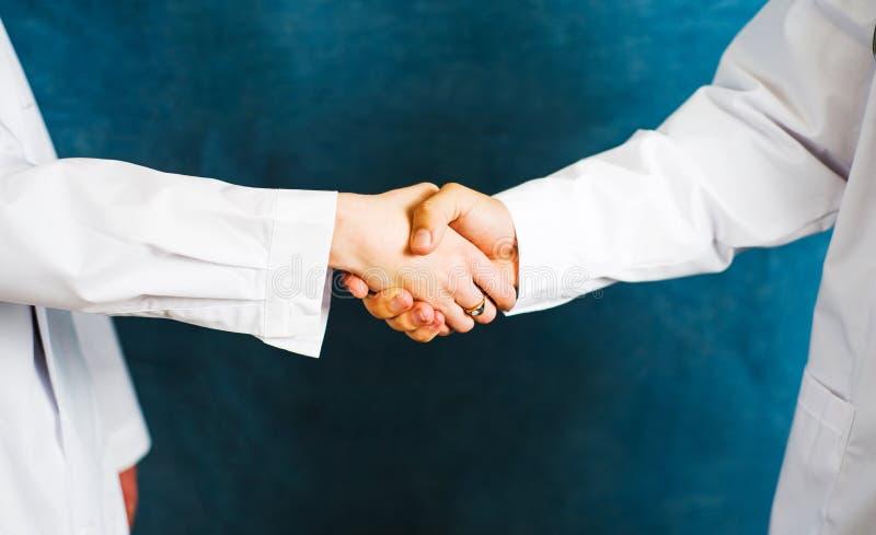 Deux médecins se serrant la main se ferment  images stock