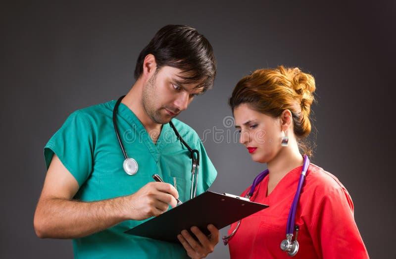 Deux médecins semblables discutant et regardant étonnés quelque chose image stock