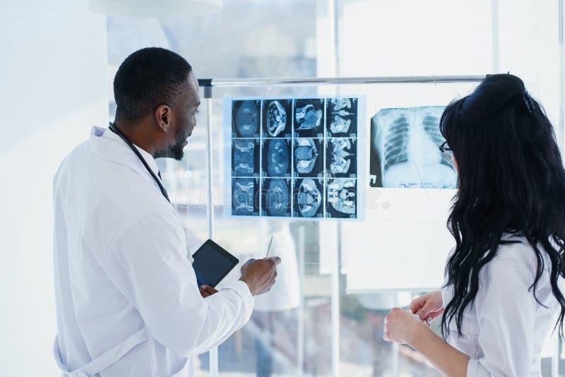 Deux m?decins regardent des rayons X m?dical Vue arrière d'homme afro-américain de médecin en chef et du regard caucasien de femm photos libres de droits