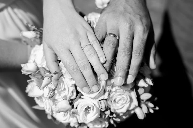 Deux mains avec des anneaux sur le bouquet de mariage de fleur photographie stock libre de droits