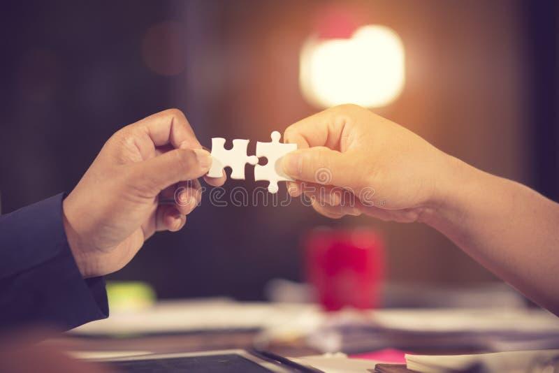 Deux mains d'homme d'affaires pour relier le morceau de puzzle de couples au fond de ciel Seul puzzle en bois denteux contre des  image stock