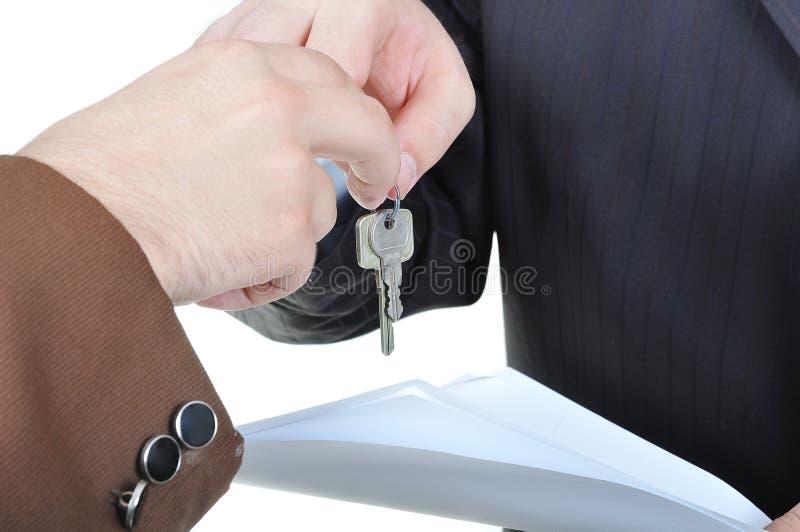 Deux mains d'hommes d'affaires et la clé photos stock