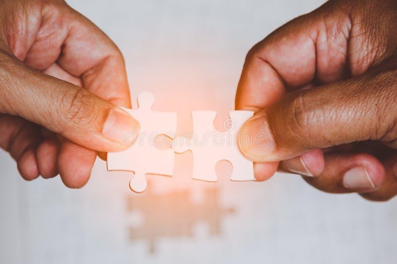 Deux mains des hommes reliant les morceaux de couples de puzzle blanc photographie stock libre de droits