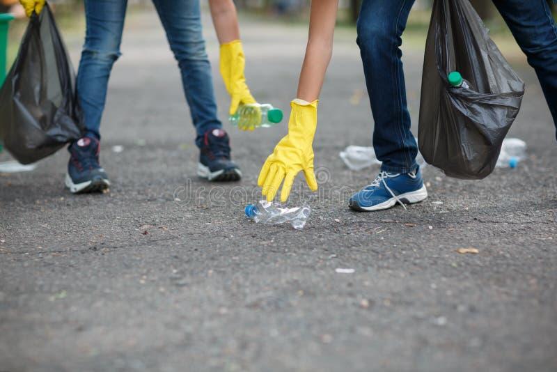 Deux mains du ` s d'enfants dans les gants jaunes de latex tenant les sacs de déchets noirs sur un fond d'asphalte Protection d'é image stock