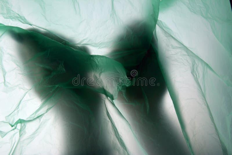 Deux mains et un sachet en plastique Les mains écrase le paquet dans des ses poings Concept de sachet en plastique avec l'espace  image stock