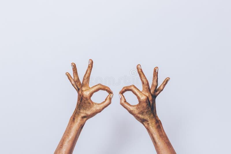 Deux mains femelles ont couvert le scintillement d'or image libre de droits