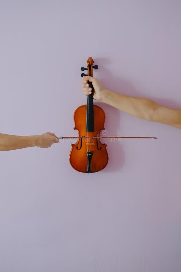 Deux mains jouant le violon sur le fond pourpre photos stock