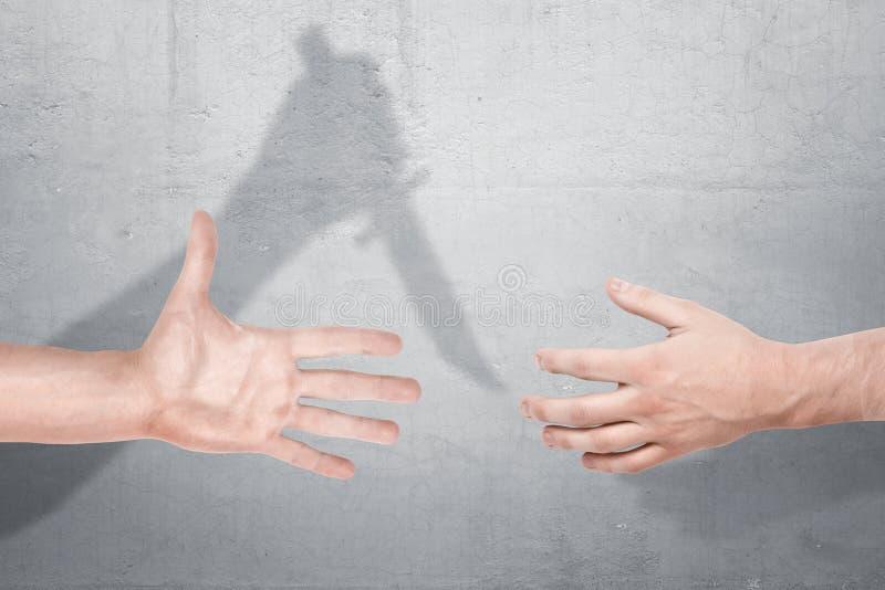 Deux mains masculines obtenant étroitement pour une poignée de main avec une ombre d'une main tenant un couteau sur un fond concr image stock