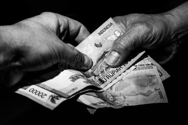 Deux mains, une indonésienne et une du blanc caucasien remettant les billets de banque indonésiens entre eux images stock
