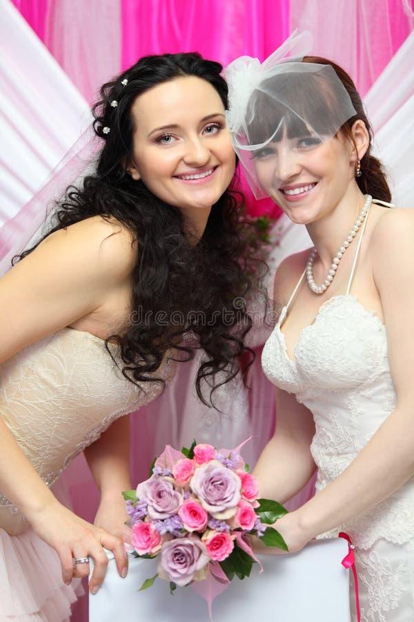 Deux mariées portant les robes blanches retiennent le bouquet photos libres de droits