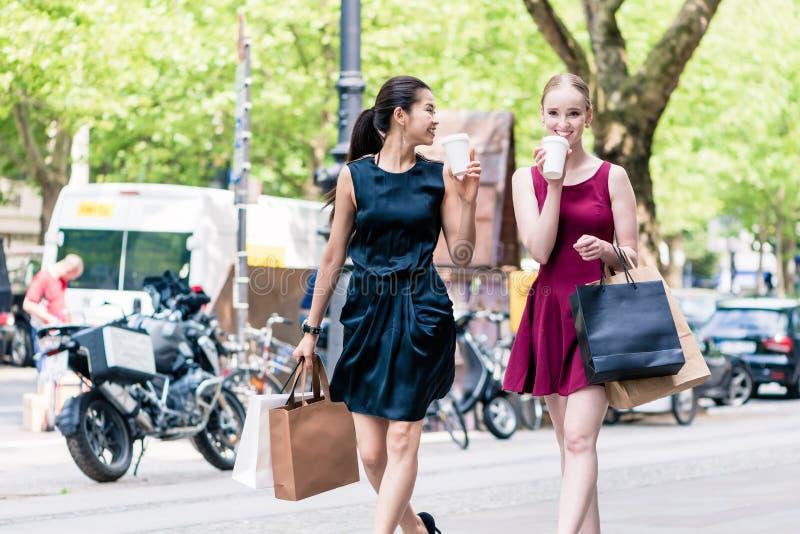 Deux meilleurs amis féminins buvant du café tandis que f du centre de marche photo stock