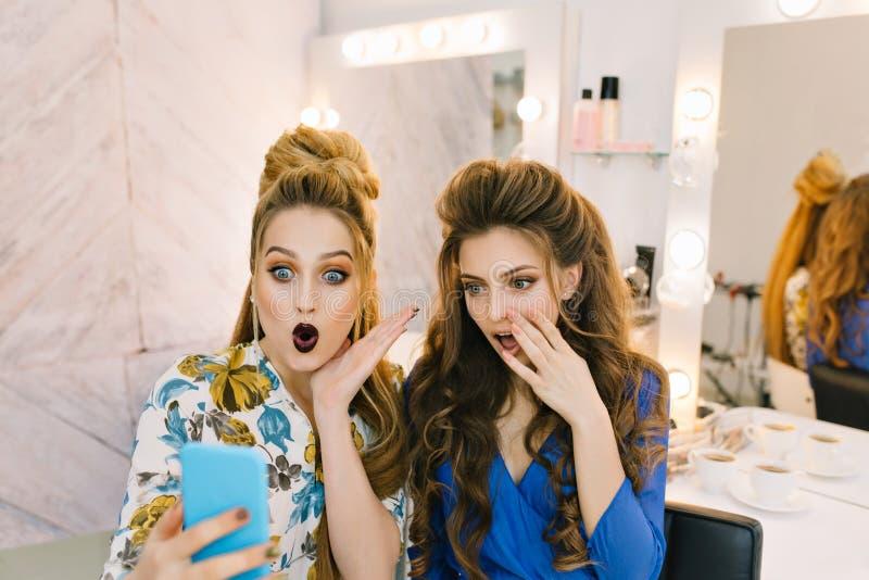 Deux modèles attrayants à la mode avec les makeups élégants, coiffures de luxe ayant l'amusement ensemble dans le salon de haidre photo libre de droits
