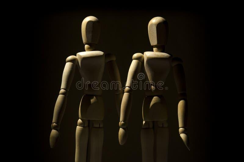 Deux modèles en bois de mannequin sur le fond foncé images stock
