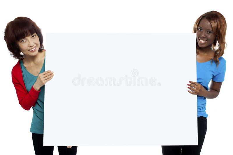 Deux modèles femelles ethniques présentant le whiteboard photographie stock libre de droits