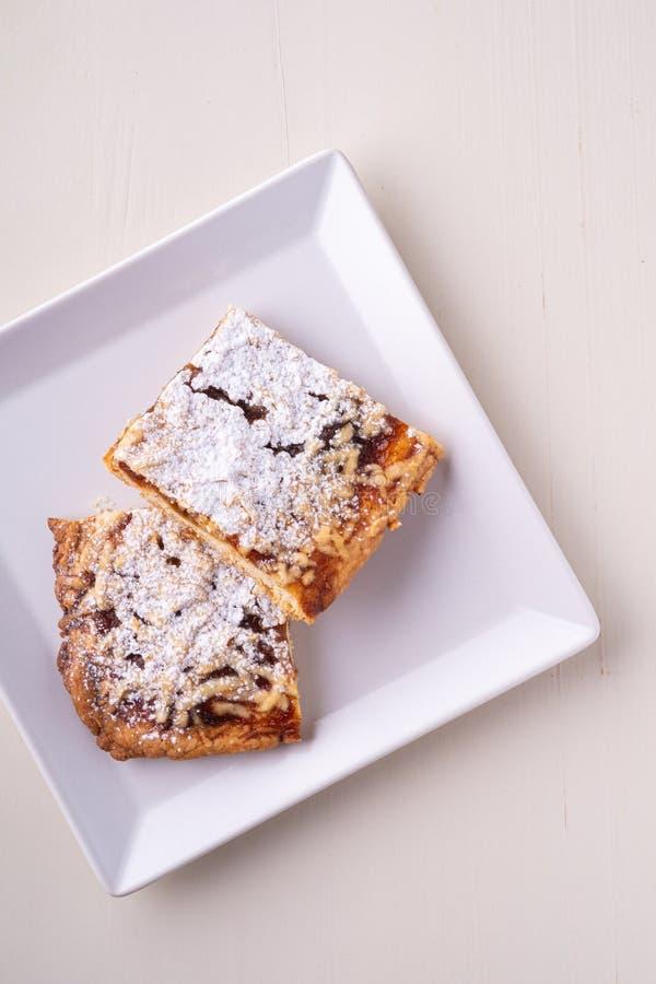 Deux morceaux d'abricot fait maison de biscuits bloquent le sucre en poudre dans le plat carré blanc photographie stock libre de droits