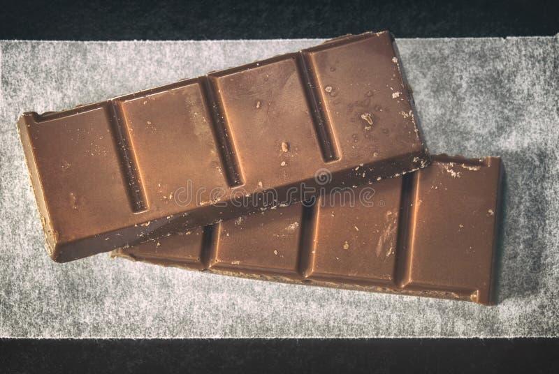 Deux morceaux de barres de chocolat sur le plan rapproché de papier parcheminé images libres de droits