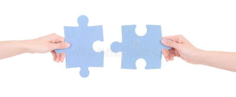 Deux morceaux de puzzle chez des mains de la femme d'isolement sur le blanc photos stock