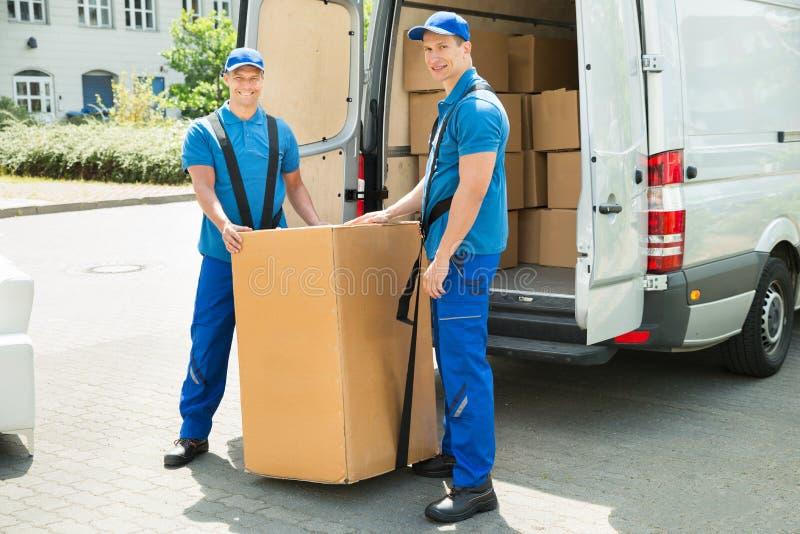 Deux moteurs chargeant des boîtes dans le camion images stock