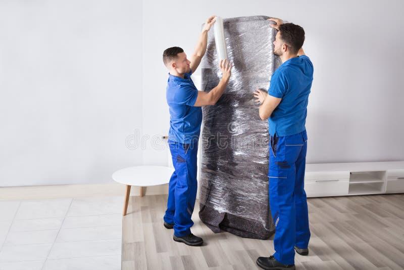 Deux moteurs masculins emballant des meubles image stock