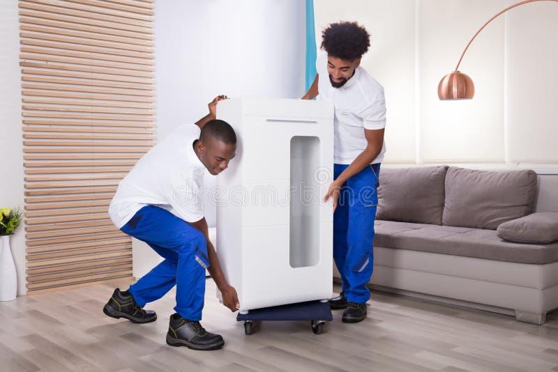 Deux moteurs masculins plaçant le Cabinet blanc sur la roue images stock