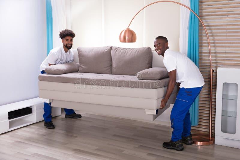 Deux moteurs masculins plaçant le sofa photos libres de droits