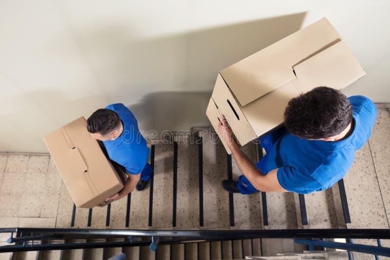 Deux moteurs portant des boîtes en carton sur l'escalier images stock