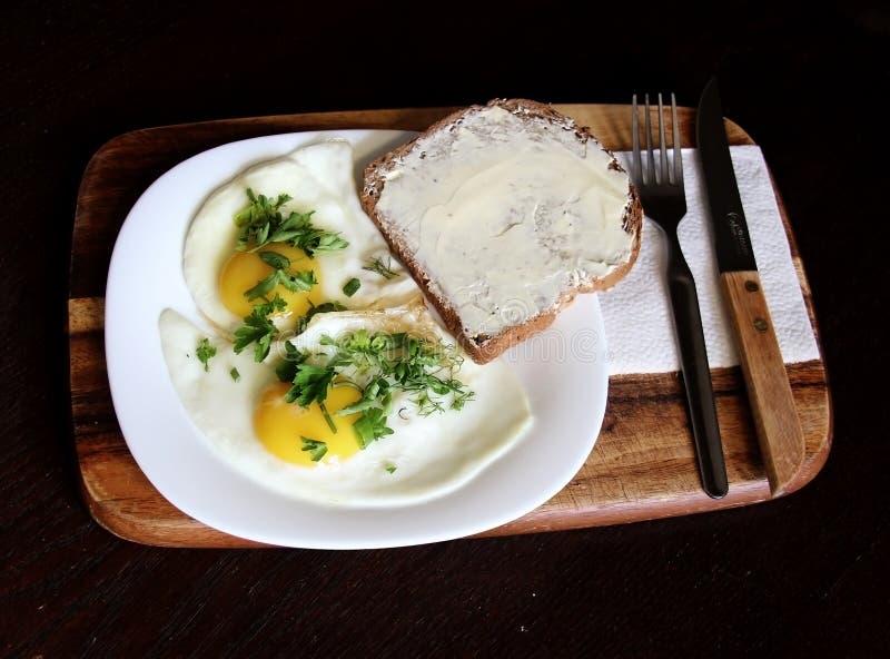 Deux oeufs au plat avec du pain et beurre et persil coupé photo stock